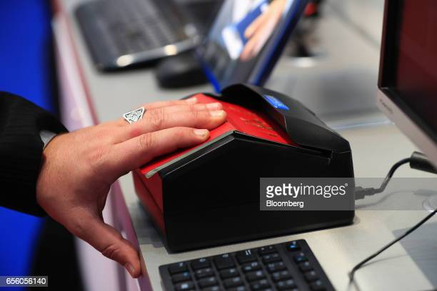 An exhibitor places a passport on a scanning device at the Dermalog Identification Systems GmbH pavilion at the CeBIT 2017 tech fair in Hannover...
