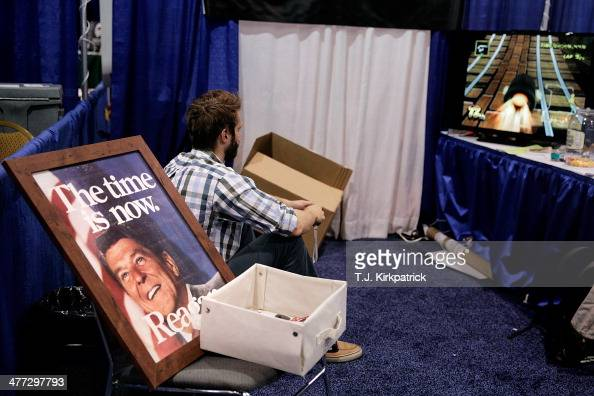 An exhibitor plays a video game in their booth during the 41st annual Conservative Political Action Conference at the Gaylord International Hotel and...