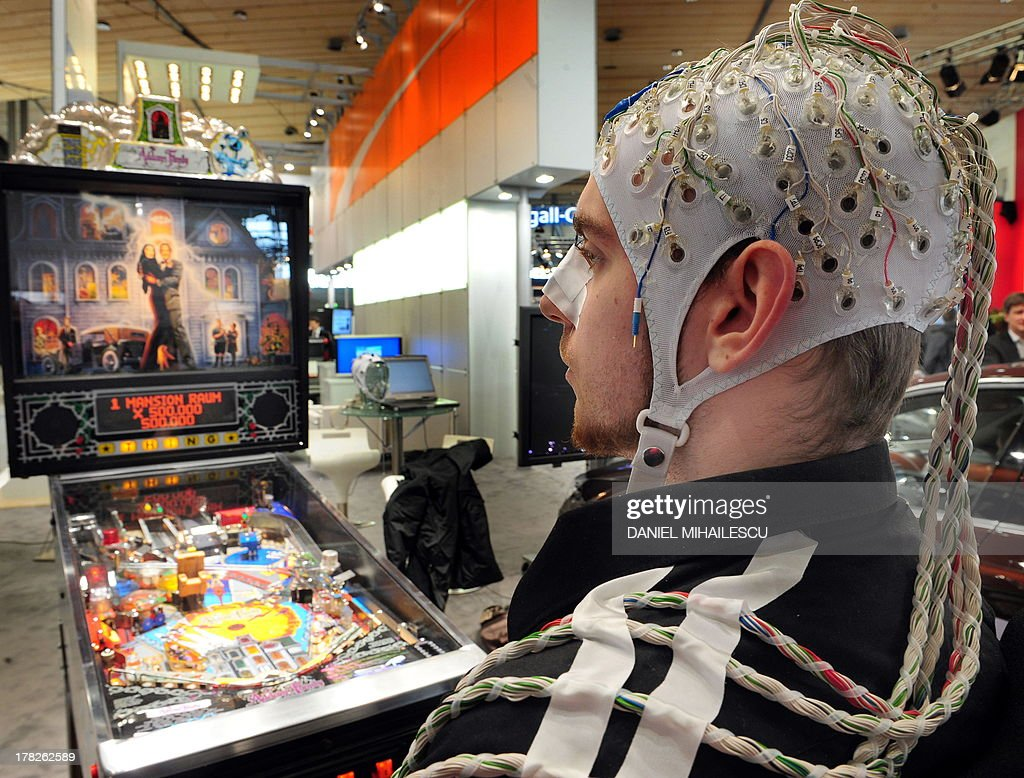 An exhibitor plays on a flipper machine using an EEG to measure neurons in the brain at the world's biggest hightech fair the CeBIT on March 3 2010...