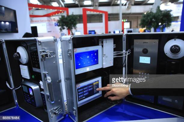 An exhibitor prepares a display of Alhua Technology video intercom products in the Zheijiang Dahua Technology Co Ltd pavilion at the CeBIT 2017 tech...