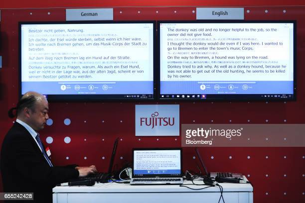 An exhibitor prepares a display of the 'Livetalk' live translation app in the Fujitsu Ltd pavilion at the CeBIT 2017 tech fair in Hannover Germany on...