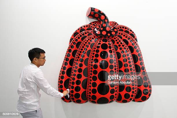 An exhibitor prepares the art installation titled 'I Carry On Living With The Pumpkins' by artist Yayoi Kusama at Marina Bay Sands Expo and...