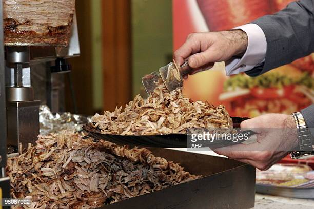 An exhibitor serves kebab meat from a new doner kebabcutting robot during the 'Doga' the doner gastronomy trade fair in Berlin on March 27 2010 Doner...