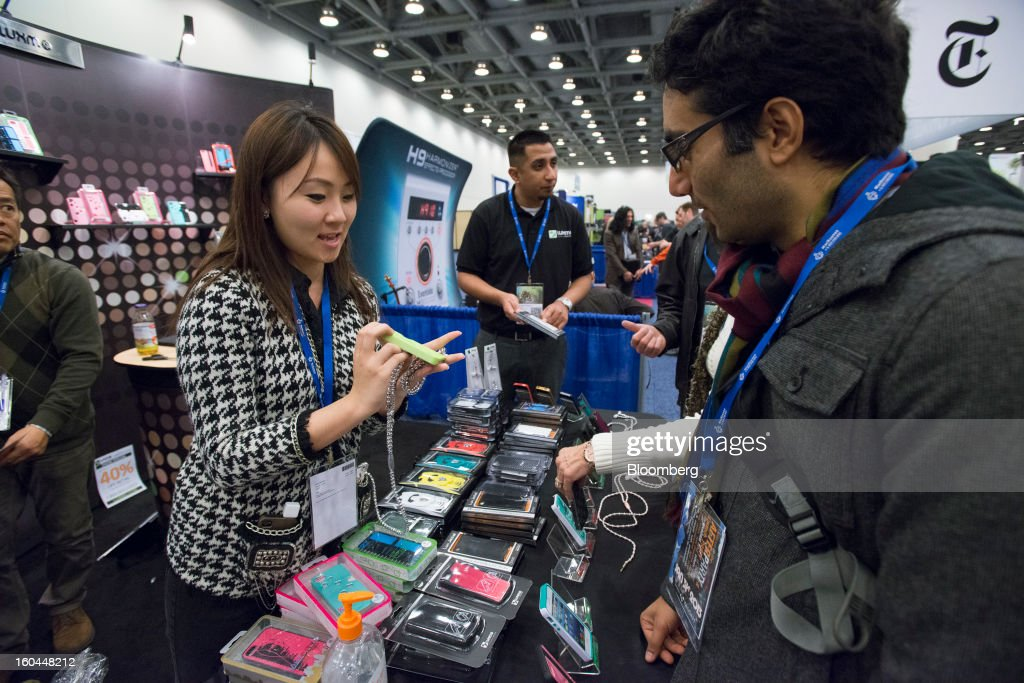 An exhibitor shows new cases for Apple Inc. iPhones to an attendee at the Macworld/iWorld conference at the Moscone Center West in San Francisco, California, U.S., on Thursday, Jan. 31, 2013. This year's conference, titled 'The Ultimate iFANEvent,' brings together attendees to celebrate Apple Inc. technology and learn more about products and services for Apple users. Photographer: David Paul Morris/Bloomberg via Getty Images