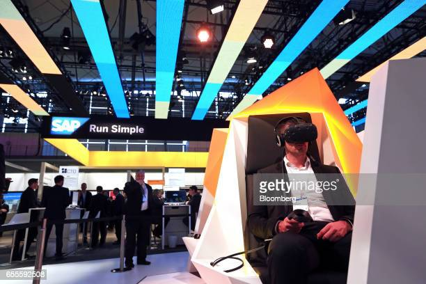 An exhibitor sits in a booth and demonstrates a Virtual Reality device in the SAP SE pavilion at the CeBIT 2017 tech fair in Hannover Germany on...