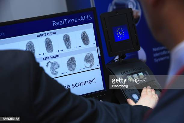 An exhibitor tests a Dermalog LF10 biometric fingerprint scanner at the Dermalog Identification Systems GmbH pavilion at the CeBIT 2017 tech fair in...