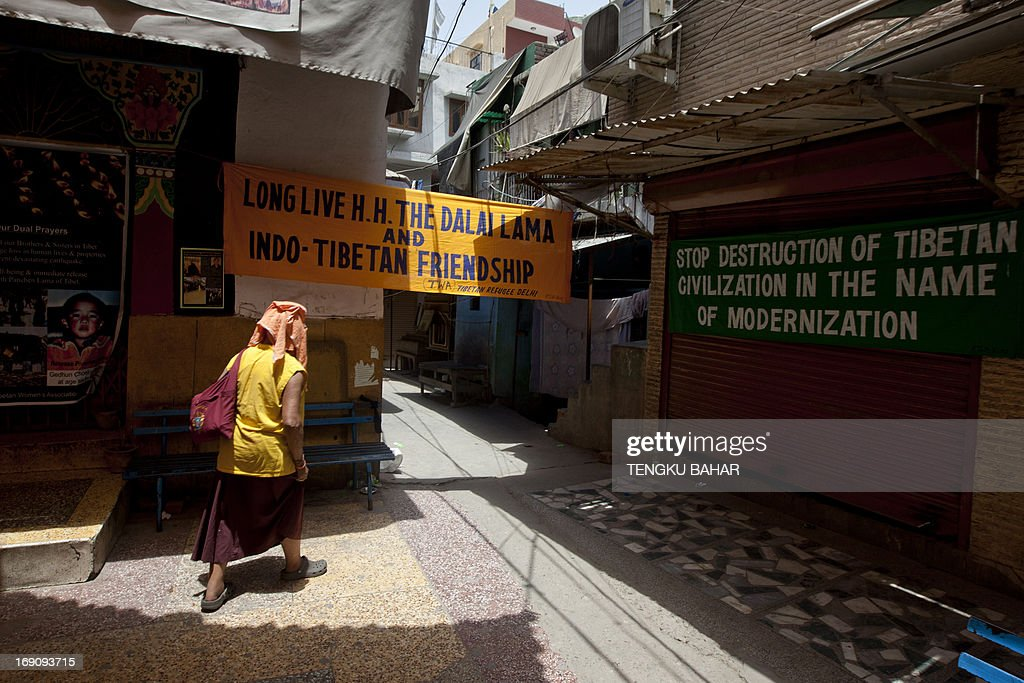 An exile Tibetan monk walks past banners, erected in protest against the visit of Chinese Premier Li Keqiang, in front of shuttered shops at the Tibetan refugee colony of Majnu Ka Tilla in New Delhi on May 20, 2013. Indian Prime Minister Manmohan Singh said he had agreed with his Chinese counterpart to make a new push to settle a long-running border row, pledging his commitment to 'peace and tranquillity'.