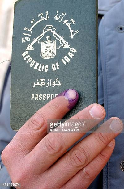 An exiled Iraqi holds his passport with an inkstained finger after voting in his country's first elections since the fall of deposed dictator Saddam...