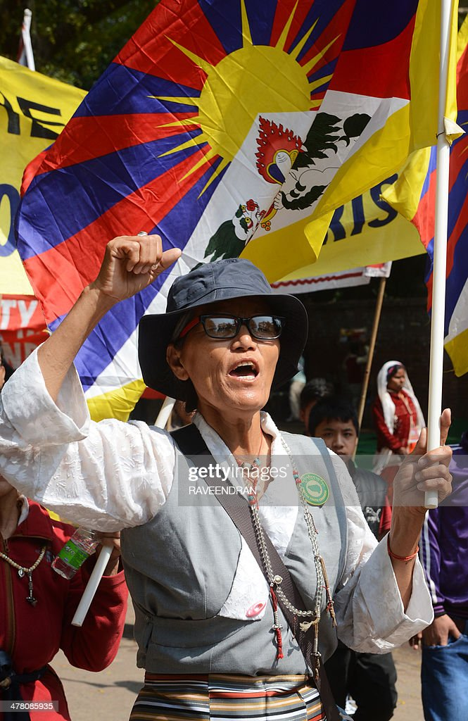 An exiled Tibetan activist holds a Tibetan flag and shouts anti-China slogans during a protest marking the 55th anniversary of the 1959 Tibetan uprising against Chinese rule in India's capital New Delhi on March 12, 2014. Tibetan anger at Beijing's control simmered for decades and erupted into violent riots against Chinese rule in the Tibet regional capital Lhasa and adjacent areas in March 2008. Since 2009, more than 120 Tibetans have set themselves on fire to protest at China's rule and at least 90 have died. AFP PHOTO/RAVEENDRAN