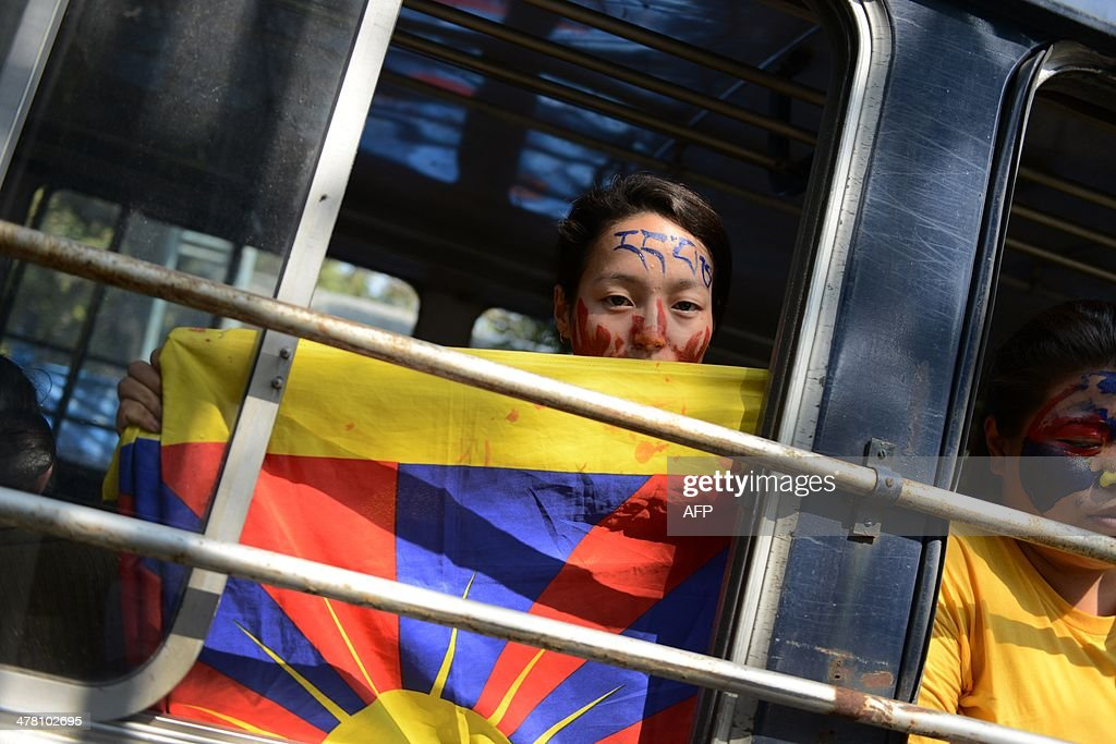 An exiled Tibetan activist holds her national flag from a police bus at the Chanakyapuri police station after she was detained during a protest outside the Chinese Embassy to mark the 55th anniversary of the 1959 Tibetan uprising against Chinese rule in New Delhi on March 12, 2014. Tibetan anger at Beijing's control simmered for decades and erupted into violent riots against Chinese rule in the Tibet regional capital Lhasa and adjacent areas in March 2008. Since 2009, more than 120 Tibetans have set themselves on fire to protest at China's rule and at least 90 have died. AFP PHOTO/Chandan KHANNA