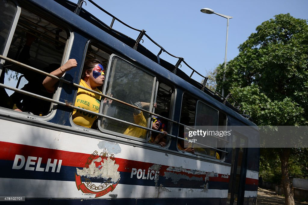 An exiled Tibetan activist shouts anti-China slogans from a police bus at the Chanakyapuri police station after she was detained during a protest outside the Chinese Embassy to mark the 55th anniversary of the 1959 Tibetan uprising against Chinese rule in New Delhi on March 12, 2014. Tibetan anger at Beijing's control simmered for decades and erupted into violent riots against Chinese rule in the Tibet regional capital Lhasa and adjacent areas in March 2008. Since 2009, more than 120 Tibetans have set themselves on fire to protest at China's rule and at least 90 have died. AFP PHOTO/Chandan KHANNA