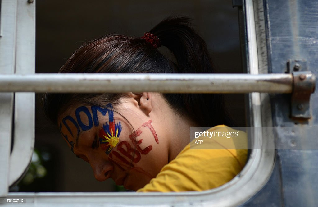 An exiled Tibetan activist sits in a police bus at the Chanakyapuri police station after she was detained during a protest outside the Chinese Embassy to mark the 55th anniversary of the 1959 Tibetan uprising against Chinese rule in New Delhi on March 12, 2014. Tibetan anger at Beijing's control simmered for decades and erupted into violent riots against Chinese rule in the Tibet regional capital Lhasa and adjacent areas in March 2008. Since 2009, more than 120 Tibetans have set themselves on fire to protest at China's rule and at least 90 have died. AFP PHOTO/Chandan KHANNA