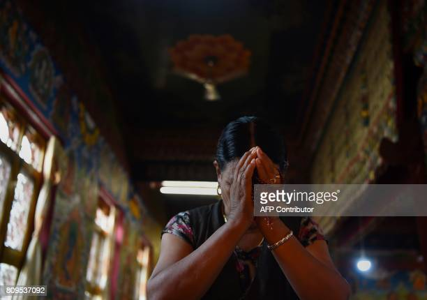 TOPSHOT An exiled Tibetan Buddhist performs rituals in front of a portrait of spiritual leader the Dalai Lama during events to mark his birthday at...