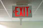 An exit sign hanging from a ceiling