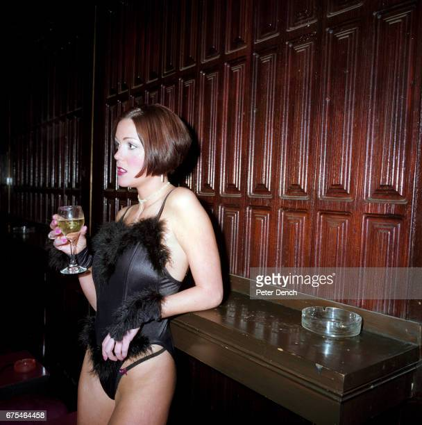 An exotic dancer with a glass of white wine at SophistiCats Gentlemen's Club in central London March 2001