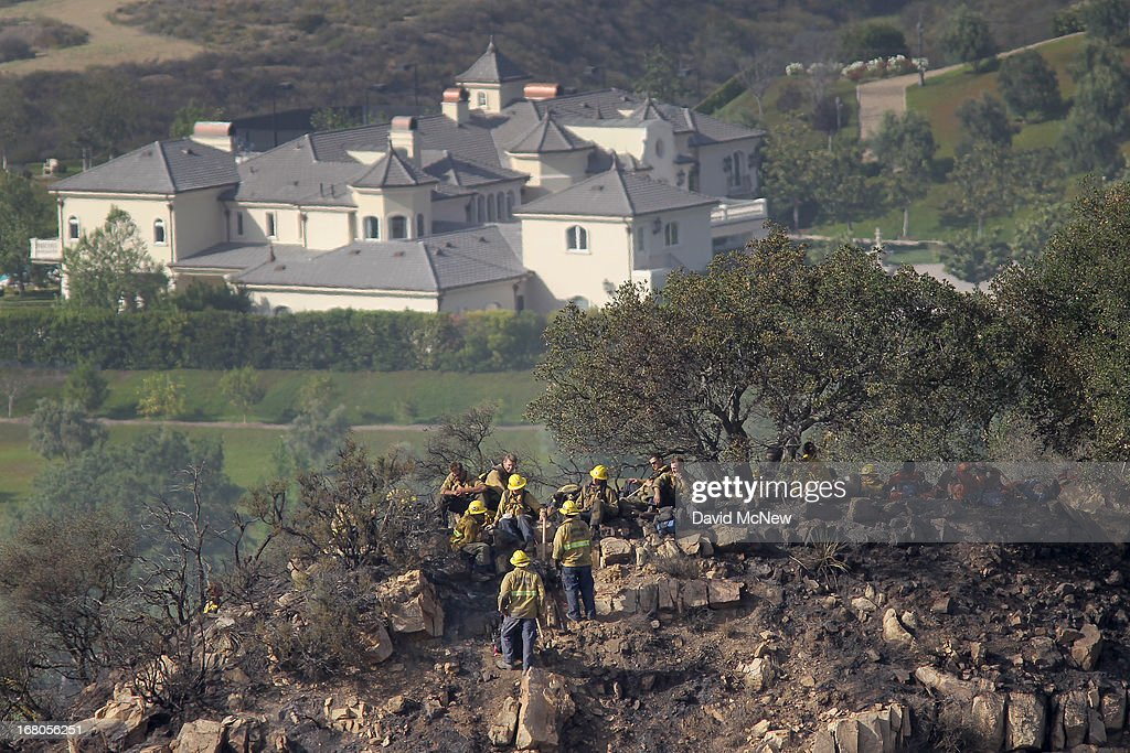 An expansive luxury home sits in the distance as firefighters take a break while constructing firelines by hand at the Springs fire on May 4, 2013 near Camarillo, California. Improving weather conditions are helping firefighters get the upper hand on the wildfire which has grown to 28,000 acres and is now 56 percent contained.