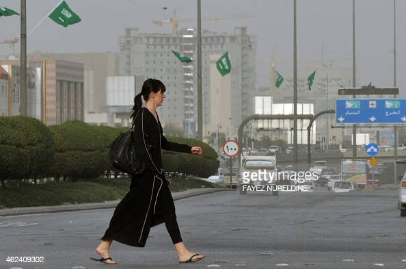 An expatriate crosses a main street on February 18 2011 in the Saudi capital Riyadh decorated with national flags on the eve of King Abdullah bin...
