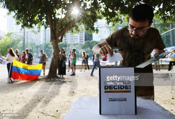 An expatriate Venezuelan casts his ballot as others wait on line during an unofficial referendum or plebiscite held by Venezuela's opposition against...