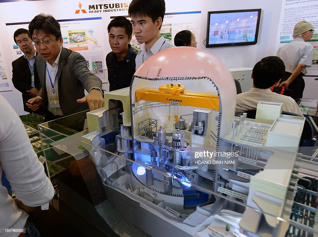 An expert from Japan's Mitsubishi Heavy Industries (2nd L) presents a nuclear reactor model on display at an international nuclear power exhibition being held in Hanoi on October 26, 2012. Vietnam plans to begin building its first nuclear power plant in 2014 with the Russian State Atomic Energy Corporation or 'Rosatom' as its contractor. AFP PHOTO/HOANG DINH Nam