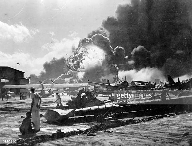 An explosion at the Naval Air Station Ford Island Pearl Harbour during the Japanese attack Sailors stand amid wrecked watching as the USS Shaw...