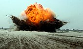 An explosion erupts from the detonation of a weapons cache.