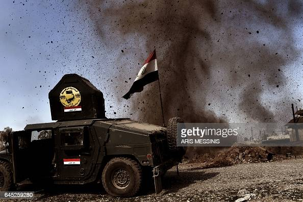 TOPSHOT An explosion hits near a vehicle belonging to Iraq's elite Rapid Response Division during the assault to retake the northern city of Mosul as...