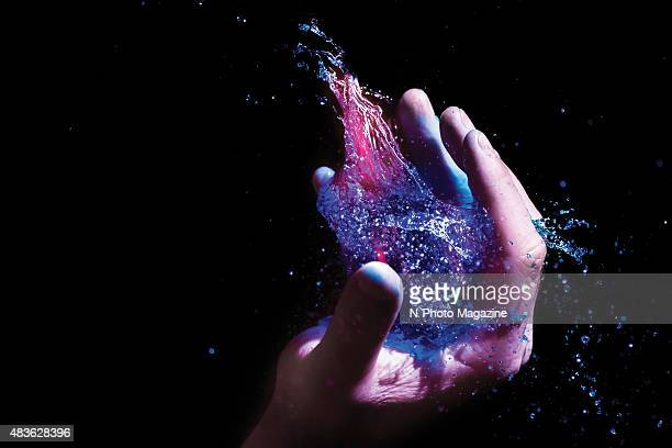 An explosion of coloured water in the plan of a hand taken on September 24 2014