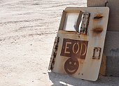 An Explosive Ordnance Disposal logo is painted on an old vehicle door at one of the ranges at Ali Air Base, Iraq.
