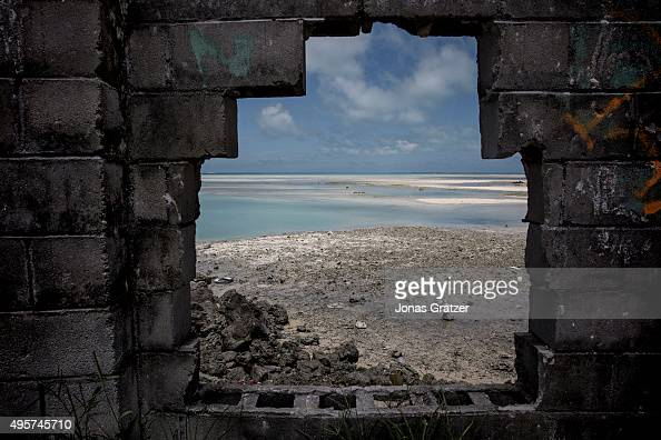 An exposed seabed viewed through a hole in a wall on an island in Kiribati The people of Kiribati are under pressure to relocate due to sea level...