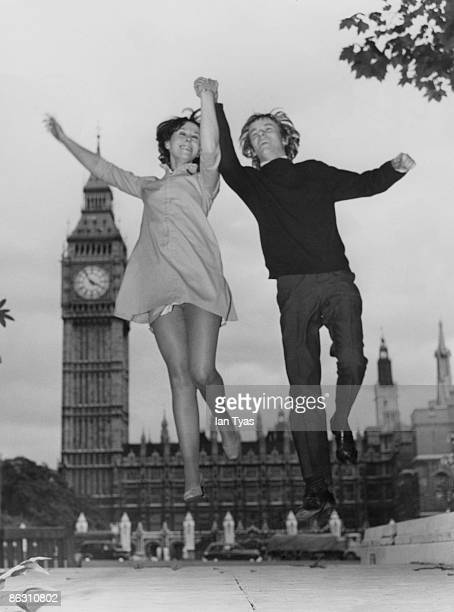 An exuberant young couple leap into the air in front of the Houses of Parliament in London 5th September 1967