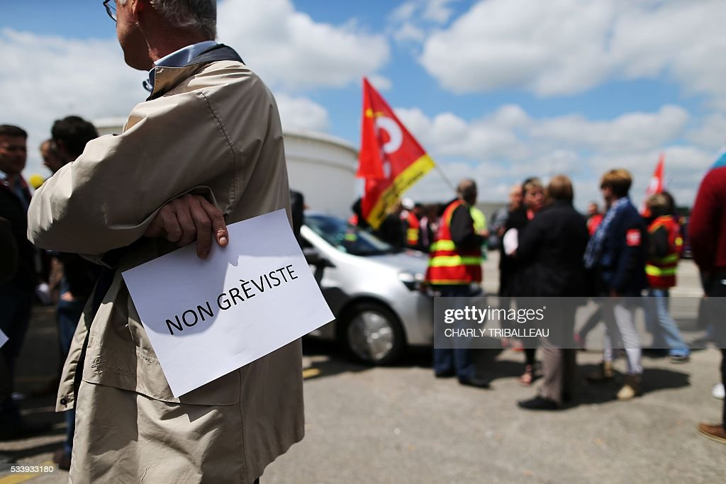 An Exxon employee holds a sign reading 'Non striker' as he stands near French CGT union members at the ExxonMobil oil refinery in Notre-Dame-de-Gravenchon, northwestern France, on May 24, 2016, during blockades and strikes at several oil refineries and fuel depots in France by protesters opposed to government labour reforms. A strike called by the Force Ouvriere (FO) and General Confederation of Labour (CGT) French workers' unions started slowing on May 24 at the ExxonMobil oil refinery in Notre-Dame-de-Gravenchon, without disrupting operations at France's second largest refinery. Six out of eight of the refineries in France have either stopped operating or have reduced output due to strikes and blockades. / AFP / CHARLY