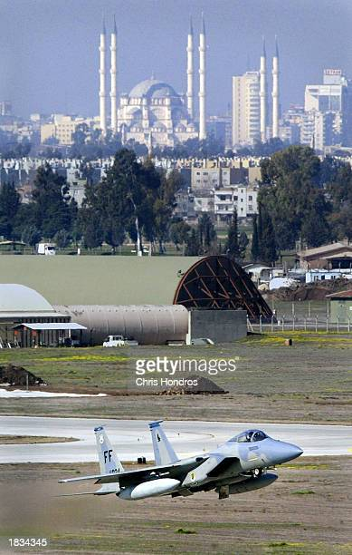 An F15 fighter jet glides in for a landing in front of Adana's main mosque March 7 2003 at Incirlik Air Force Base in Turkey Activity at Incirlik one...