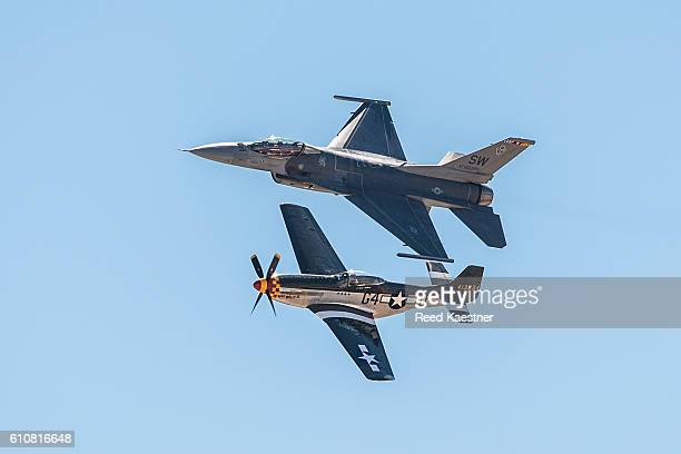 An F-16 and P-51 Mustang fly in close formation