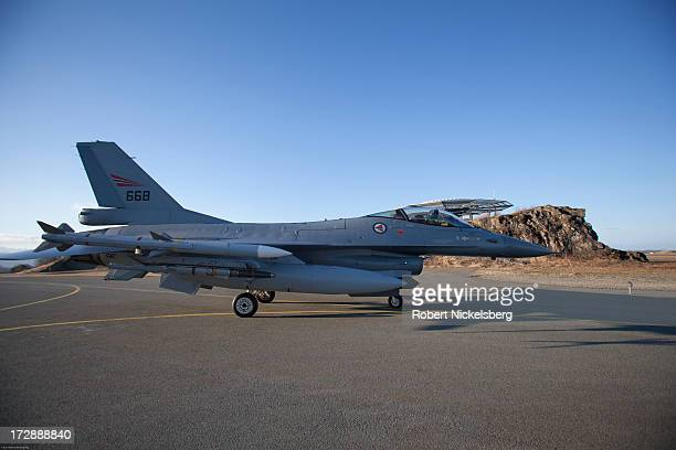An F16 pilot with the Norwegian Air Force readies his plane down a ramp to a runway before taking off March 1 2013 above the Arctic Circle in Bodo...