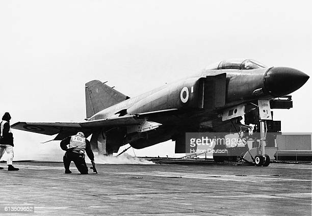 An F4 Phantom fighter jet is prepared for takeoff from the HMS Eagle aircraft carrier | Location Near England UK