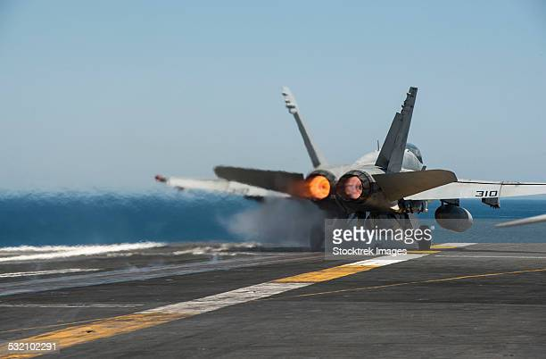 An F/A-18C Hornet launches from the flight deck of USS Carl Vinson.