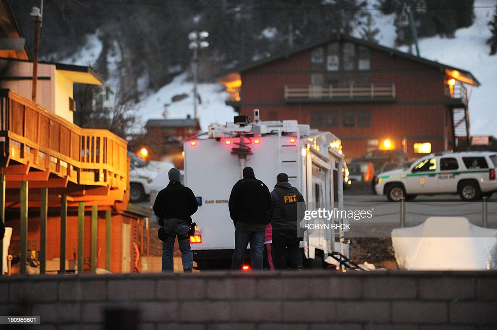 An FBI agent and other law enforcement officials are seen at a police commander center in Big Bear, California during the manhunt for alleged triple murder Dorner, February 7, 2013. US police were searching Thursday in and around the California mountain resort for Dorner, 33, an alleged fugitive cop killer, after his car was found burnt out in nearby woods, officials said.