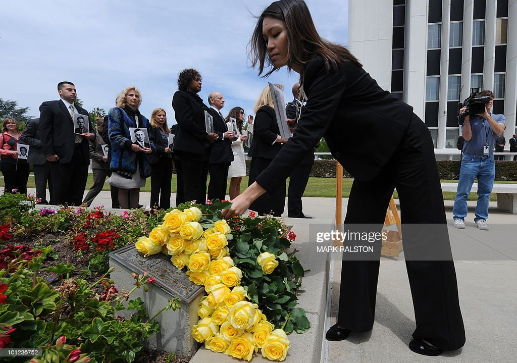 An FBI agent places a flower on a memorial as other agents hold photos of deceased colleagues, during a memorial service for Special Agents and their law enforcement and military colleagues killed in the line of duty, at the Federal Building in Los Angeles on May 28, 2010. Memorial Day, which was formerly known as Decoration Day, commemorates US men and women who died while in the service to their country and was first enacted to honor Union soldiers of the American Civil War. AFP PHOTO/Mark RALSTON