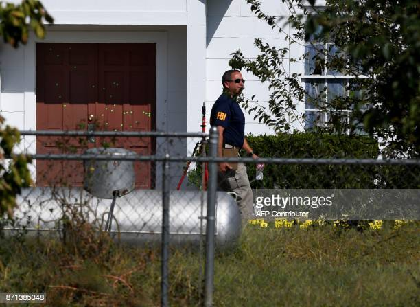 An FBI agent walks past the bullet riddled main door of the First Baptist Church after a mass shooting that killed 26 people in Sutherland Springs...
