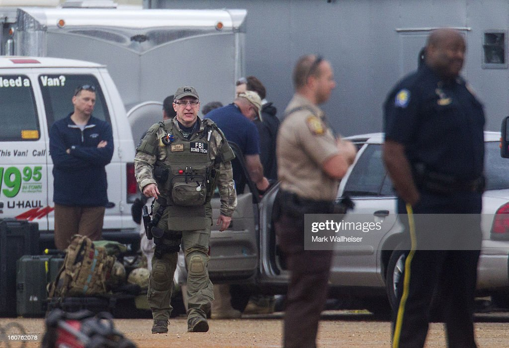 An FBI bomb technician, as well as, other agents and Alabama State Troopers prepare to walk to the bunker to process the crime scene February 5, 2013 in Midland City, Alabama.. The suspect, Jimmy Lee Dykes was killed when the FBI stormed the bunker and rescued the 5 year-old child named Ethan after 6 days of captivity.
