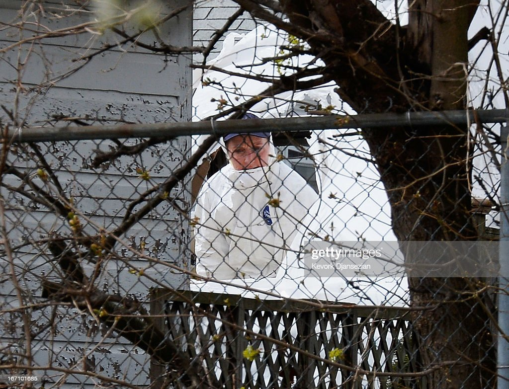An FBI investigator wearing white overall stand inside the boat where bombing suspect was hiding from police on Franklin Street on April 20, 2013 in Watertown, Massachusetts. A manhunt for Dzhokhar A. Tsarnaev, 19, a suspect in the Boston Marathon bombing ended after he was apprehended on a boat parked on a residential property in Watertown, Massachusetts. His brother Tamerlan Tsarnaev, 26, the other suspect, was shot and killed after a car chase and shootout with police. The bombing, on April 15 at the finish line of the marathon, killed three people and wounded at least 170