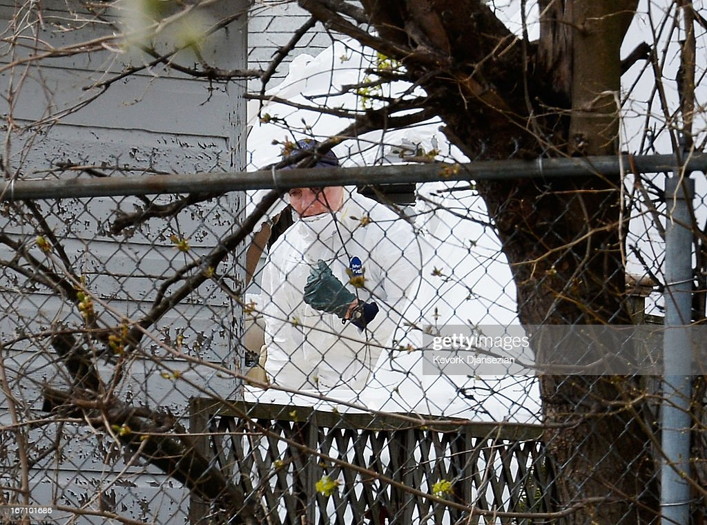 An FBI investigator wearing white overalls stands inside the boat where bombing suspect was hiding from police on Franklin Street on April 20, 2013 in Watertown, Massachusetts. A manhunt for Dzhokhar A. Tsarnaev, 19, a suspect in the Boston Marathon bombing ended after he was apprehended on a boat parked on a residential property in Watertown, Massachusetts. His brother Tamerlan Tsarnaev, 26, the other suspect, was shot and killed after a car chase and shootout with police. The bombing, on April 15 at the finish line of the marathon, killed three people and wounded at least 170