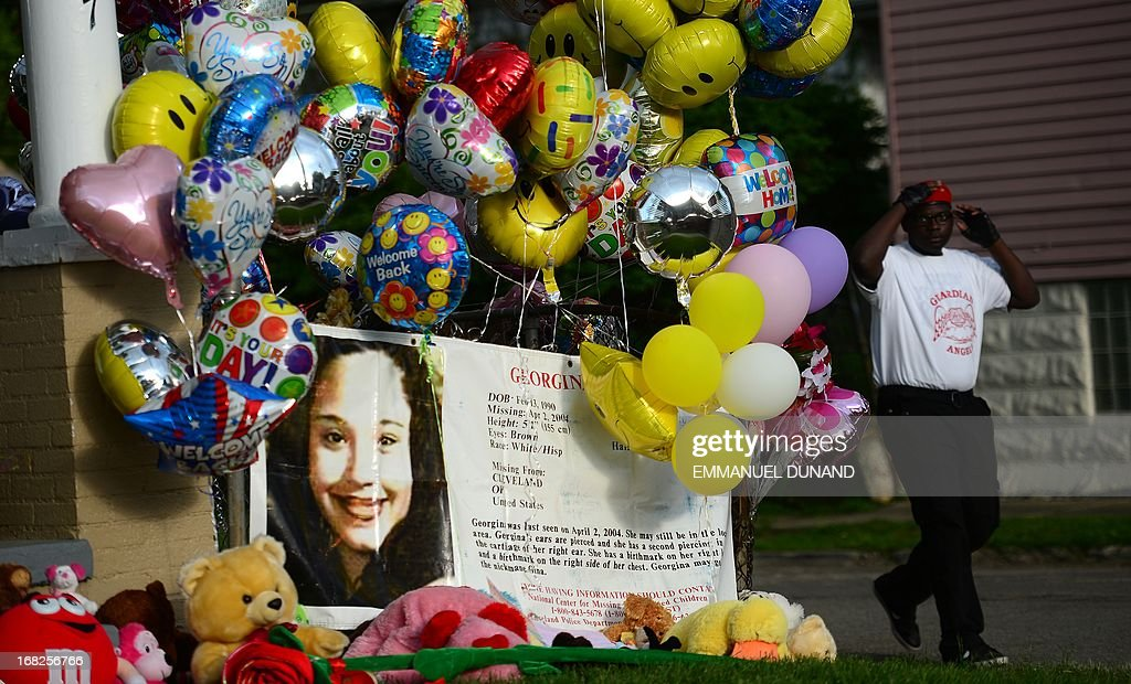 An FBI person missing sign stands in front of the family house of Gina DeJesus, one of the three women which were held captive for a decade, as it is decorated by well wishers May 7, 2013 in Cleveland, ohio. Three brothers have been arrested in connection with the kidnapping of three women found safe in a home after being missing for a decade, authorities said. There were more questions than answers the day after the stunning turn of events that began with a frantic arm sticking out of a screen door, a woman screaming for help, and a neighbor kicking in the door to free her in a working-class neighborhood of the city in the American heartland. Ariel Castro and his brothers - Pedro, 54, and Onil, 50 have been detained, authorities said. AFP PHOTO/Emmanuel Dunand