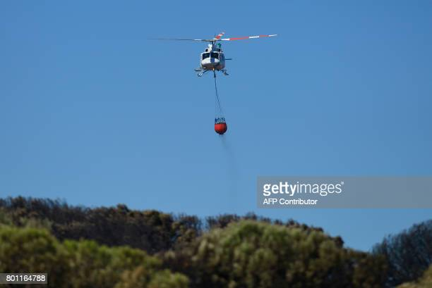 An firefighter helicopter carries water aboave after a wildifre in Mazagon next to the Donana National Park on June 26 2017 More than 1500 people...