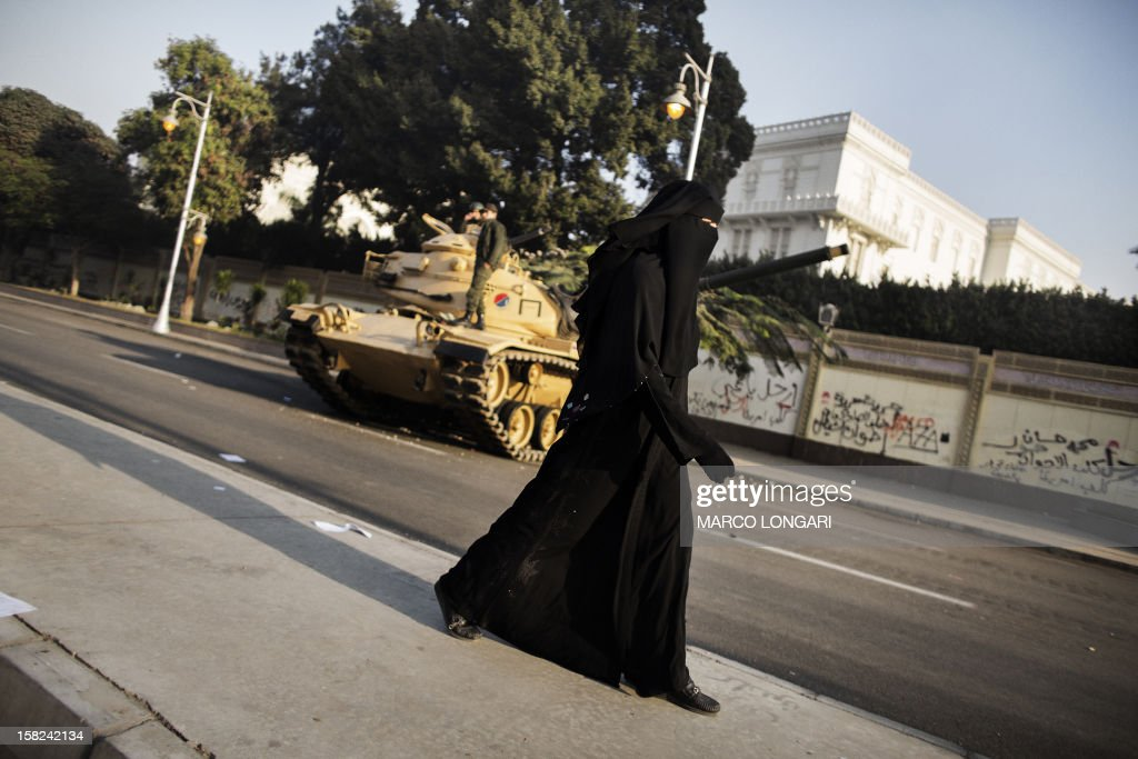 An fully-veiled Egyptian woman walks past an army tank parked outside the presidential palace in Cairo on December 12, 2012. Egypt's powerful army has called for President Mohamed Morsi and the secular opposition to meet later in the day to stop a crisis over an imminent constitutional referendum from tearing the country apart.