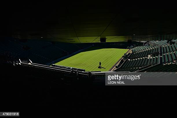 An groundsman prepares the grass on Centre Court ahead of play on day two of the 2015 Wimbledon Championships at The All England Tennis Club in...