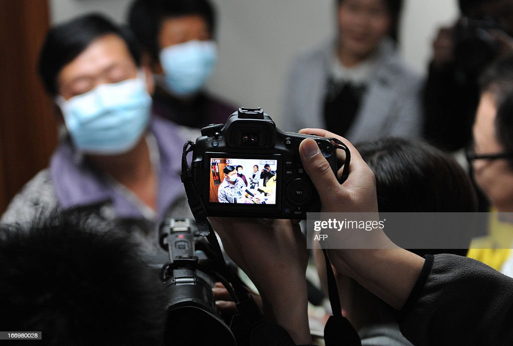 An H7N9 bird flu patient surnamed Li (L) answers questions for journalists after his recovery and approval for discharge from a hospital in Bozhou, central China's Anhui province on April 19, 2013. Experts from the UN's health agency are examining whether the H7N9 bird flu virus is spreading among humans, after a cluster of cases among relatives, but downplayed fears of a pandemic on April 19. CHINA