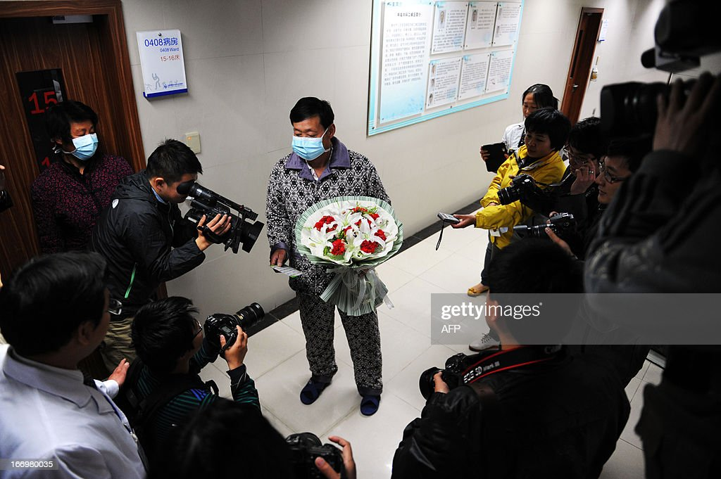 An H7N9 bird flu patient surnamed Li (C) answers questions for journalists after his recovery and approval for discharge from a hospital in Bozhou, central China's Anhui province on April 19, 2013. Experts from the UN's health agency are examining whether the H7N9 bird flu virus is spreading among humans, after a cluster of cases among relatives, but downplayed fears of a pandemic on April 19. CHINA