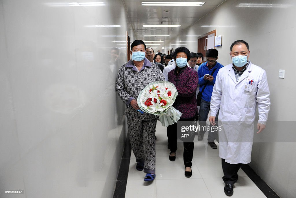 An H7N9 bird flu patient surnamed Li (C) walks in the corridor of a hospital after his recovery and approval for discharge from the hospital in Bozhou, central China's Anhui province on April 19, 2013