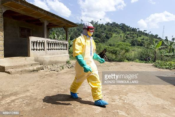 An health worker from Guinea's Red Cross wearing a Personal Protective Equipments leaves the house of a victim of the Ebola virus in Patrice...